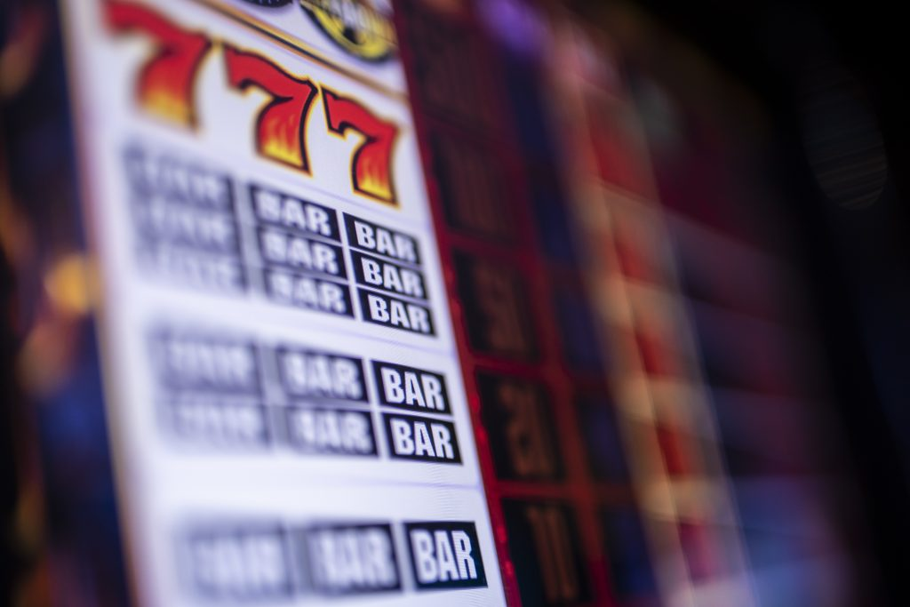 A partially blurred image of a winning slot machine with 777 and Bar Bar Bar visible