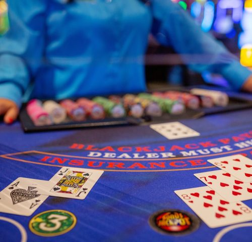 Dealer standing at blackjack table with a blackjack laid out in front