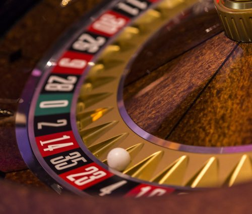 A close up of a roulette table with the ball on red 23
